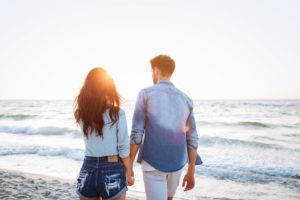 Couple walking at sunrise on the beach